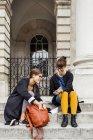 Amis féminins utilisant le téléphone intelligent — Photo de stock