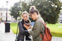 Подруги с помощью смартфона — стоковое фото