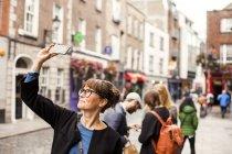 Smiling woman taking selfie — Stock Photo