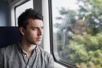 Hombre mirando por la ventana del tren - foto de stock