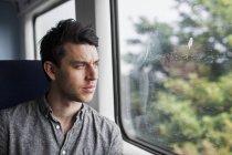 Man looking through train window — Stock Photo