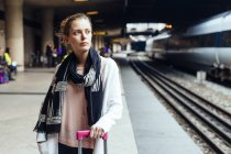 Mulher de pé na estação ferroviária — Fotografia de Stock