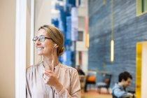 Felice donna d'affari guardando attraverso la finestra — Foto stock