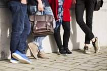 Young friends leaning against wall — Stock Photo