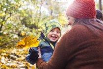 Madre con muchacho feliz con hoja - foto de stock