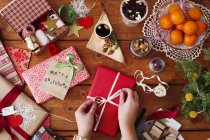 Hands tying ribbon on Christmas gift — Stock Photo