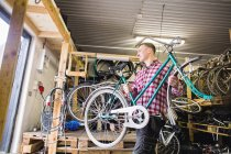 Repairman carrying bicycle in workshop — Stock Photo
