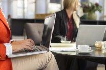 Mujer de negocios utilizando el ordenador portátil en la reunión en el restaurante - foto de stock