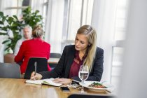 Businesswoman writing in book — Stock Photo