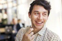 Man smiling while talking through earphones — Stock Photo
