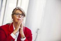 Nachdenklich Geschäftsfrau mit den Händen umklammert — Stockfoto