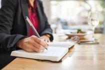 Abdomen de la femme d'affaires, écrit dans le livre — Photo de stock