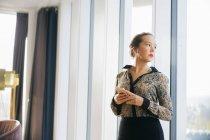 Впевнено бізнес-леді стоячи проти вікно — стокове фото