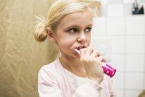 Girl brushing teeth in bathroom — Stock Photo