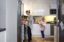 Mother preparing pancake in kitchen — Stock Photo