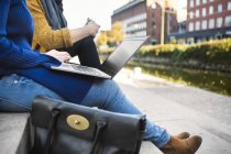 Kollegen sitzen auf Stufen und nutzen Laptops — Stockfoto