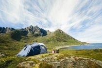 Vista traseira de pessoas sentado fora tenda — Fotografia de Stock