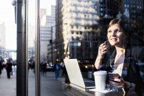 Businesswoman with headphones using laptop — Stock Photo