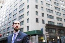 Uomo d'affari contro gli edifici in città — Foto stock