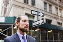 Uomo d'affari in piedi contro edifici in città — Foto stock