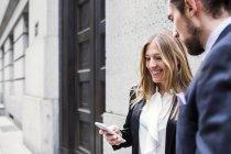 Donna di affari che mostra smartphone all'uomo — Foto stock