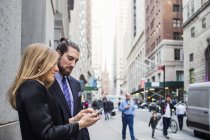 Woman showing phone to businessman — Stock Photo