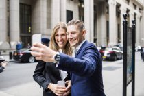 Businessman and woman taking selfie — Stock Photo