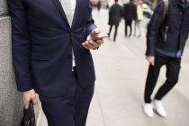 Uomo d'affari utilizzando il telefono cellulare mentre si appoggia sulla parete — Foto stock