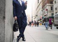 Homem de negócios segurando saco e usando smartphone — Fotografia de Stock