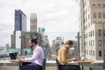 Business people working while sitting at rooftop — Stock Photo