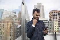 Man using phone while standing by window at rooftop — Stock Photo