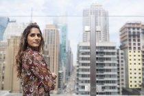 Женщина, стоя против стекло окна на крыше — стоковое фото