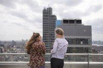 Друзья разговаривают, стоя на крыше ресторана — стоковое фото