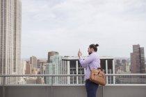Человек, фотографирование стоя на крыше с видом на город — стоковое фото