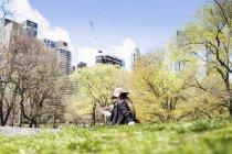Donna seduta sull'erba contro alberi ed edifici — Foto stock