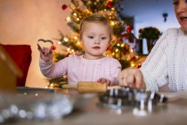 Mother and girl with cookie cutters — Stock Photo