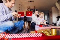Mother and father with daughter wrapping presents — Stock Photo