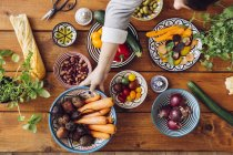 Woman picking up vegetables at wooden table — Stock Photo