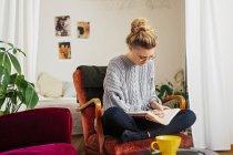 Scrittura della donna sul libro mentre sedendosi sulla sedia — Foto stock