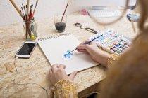 Женщина рисует на блокноте за столом — стоковое фото