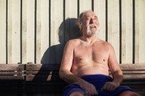 Hombre relajándose en el banco contra la pared de madera - foto de stock