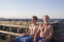 Батько й син сидять на лавці — стокове фото
