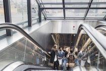 Freunde steigen auf Rolltreppe in Glashaus — Stockfoto