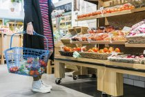 Woman holding basket while shopping in supermarket — Stock Photo