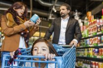 Girl sitting in cart with parents — Stock Photo