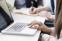Mujer de negocios usando el ordenador portátil en la mesa - foto de stock