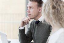 Uomo d'affari premuroso che si siede con il collega femmina — Foto stock