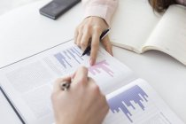 Hands pointing at graphs in meeting — Stock Photo