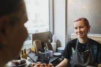 Lächelnder Besitzer sitzt im Café — Stockfoto