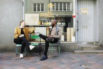 Amigos sosteniendo tazas mientras están sentados en sillas - foto de stock